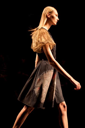 The Profile of a Model in brown yellow and black dress in Araisara Tokyo Fashion week Spring 2012 Collections