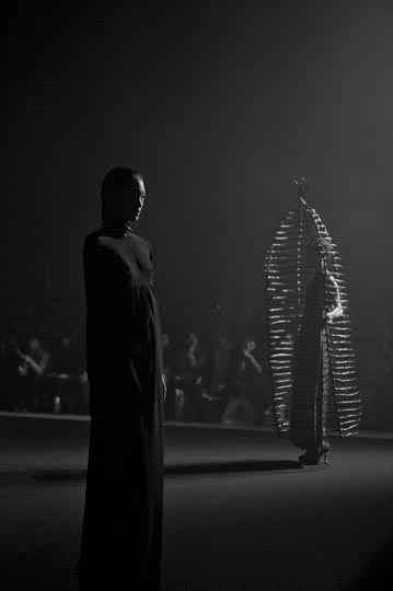 Black and white photography of two models on the runway on has a cage around her in Christian Dada Spring 2012 Collection show during tokyo Fashion week