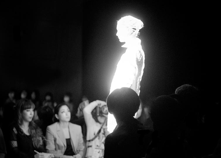 Black and white phot of a glowing model bandaged in knits walking in Johan Ku spring 2012 glow in the dark runway show tokyo fashion week photo by artist danny roberts