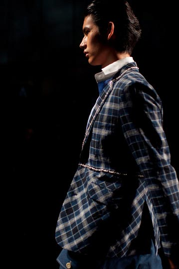 Profil of a male model in a blue ornate jack and blue pants in Keita Maruyama Spring fashion show for tokyo fashion week 2012