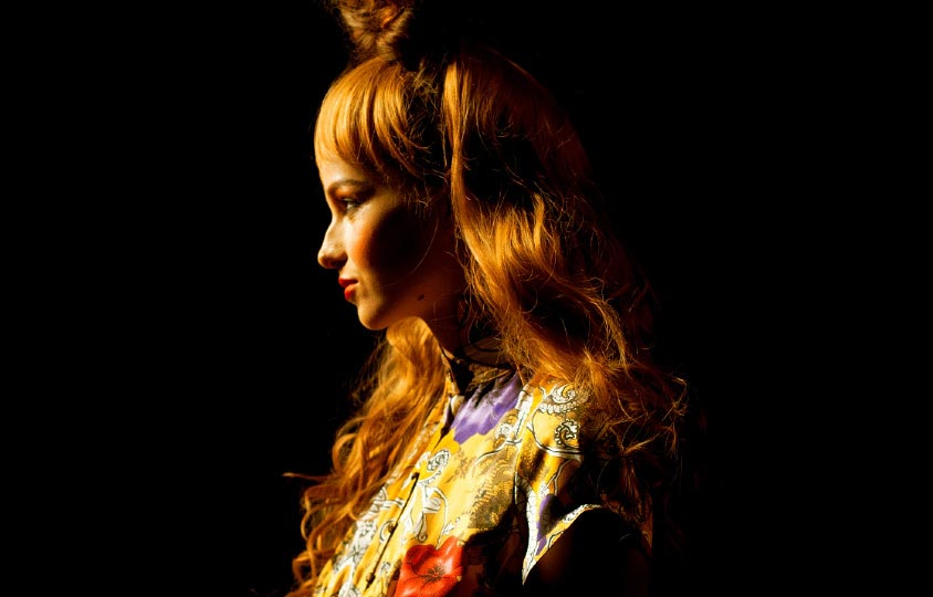 Close up of a the profile of a girl model face with large red hair and a yellow ornate dress in Motonari Ono Spring 2012 collection in Tokyo Japan Fashion week