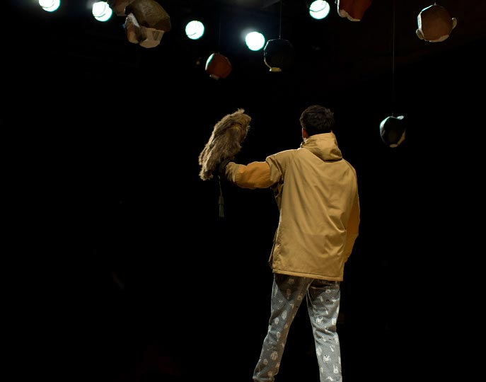 A horizontal picture of a man holding his arm up with a stuffed bird pirched on it at the end of the runday during Ne-nets show at Tokyo Fashion Week spring 2012 Photo by Artist Danny Roberts