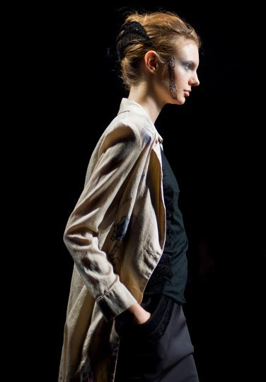 Artist Danny Roberts profile Picture of a female model in a beige over coat and black clothes underneath in Yasutoshi Exumi spring 2012 collection at tokyo fashion week